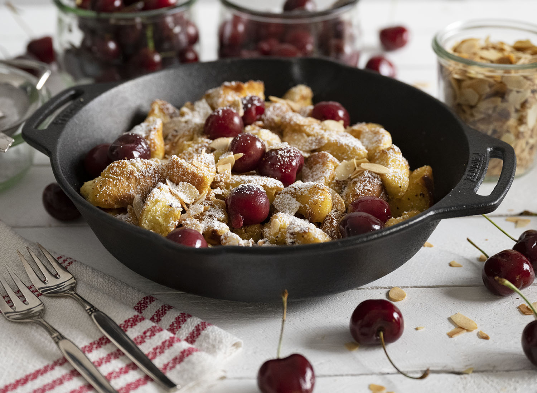 Unser Kaiserschmarrn ist fertig angerichtet. Wir servieren ihn mit warmen Kirschen und haben den gebackenen Teig mit Puderzucker besrteut.
