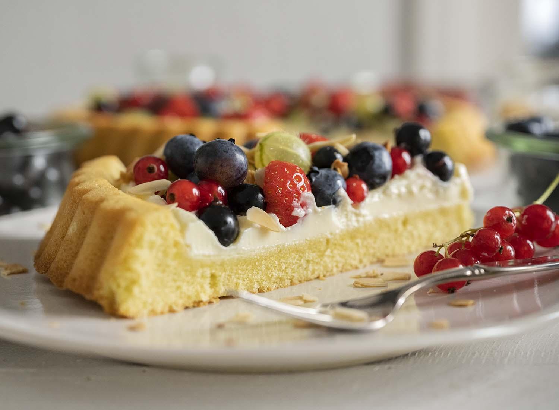 Ein STück Beerenkchen auf dem Teller. Im Hintergrund ist der ganze Kuchen zu sehen.