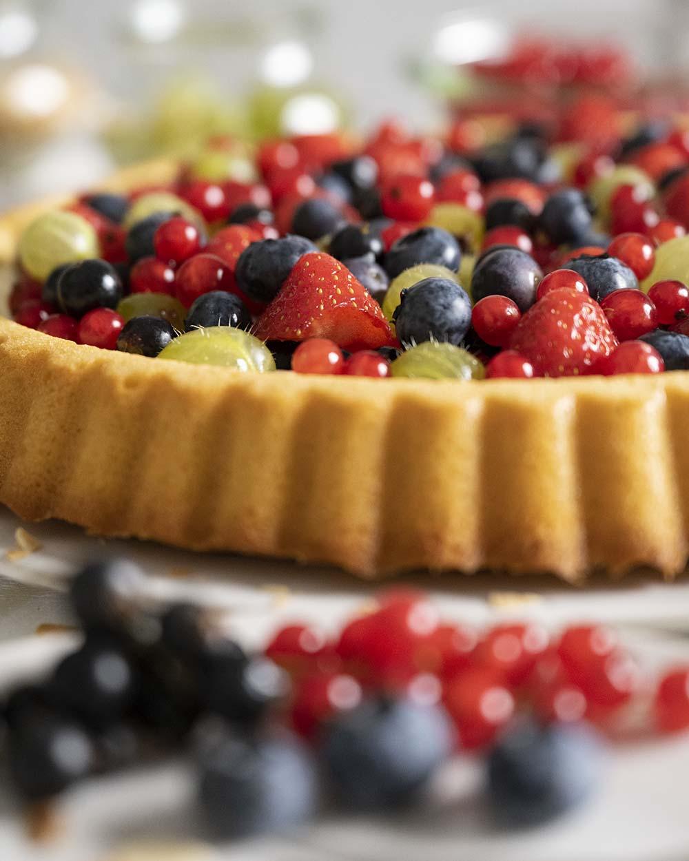 Nahaufnahme unseres Beerenkuchens: zu sehen ist auch, wie schon knusprig der Obstboden geworden ist, auf den wir eine Schicht Frischkäsecreme streichen, um ihn obenauf mit vielen bunten Beeren zu belegen.