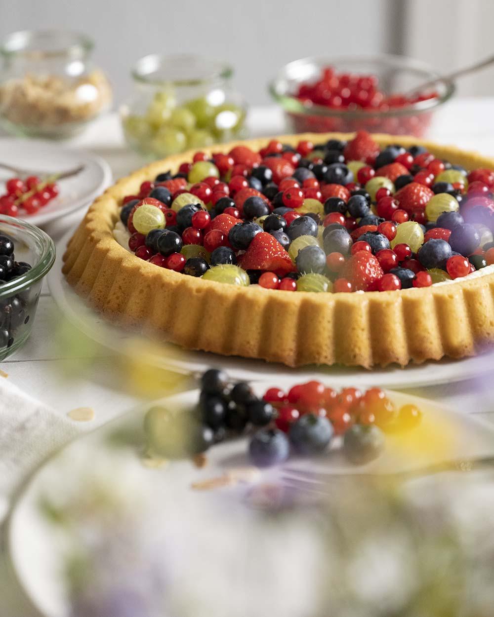 Unser Beerenkuchen steht auf der Kaffeetafel. Im Vordergrund ist ein Teller zu sehen, auf den wir gleich das erste Stück heben.