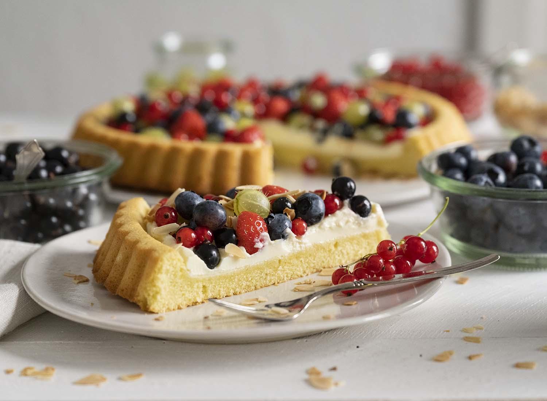 Der Blick auf die ganze Kaffeetafel: Im Vordergrund steht der Teller mit dem Stück Beerenkuchen. Im Hintergrund ist der ganze Kuchen zu sehen. Außerdem haben wir einnige Schalen mit frischen Beeren, darunter Heidelbeeren, auf den Tisch gestellt.