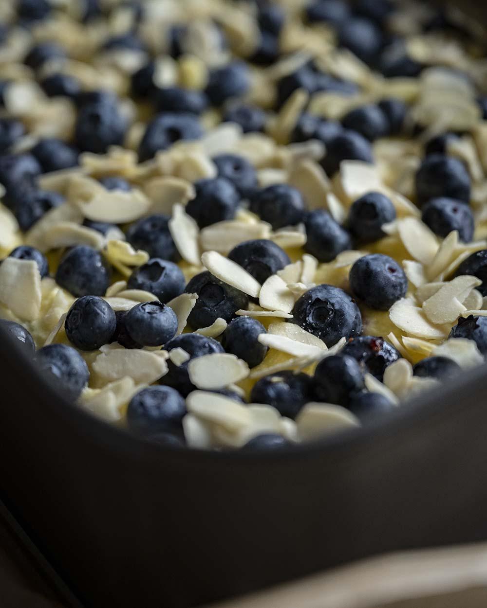 Der Teig für unseren Heidelbeer Joghurtkuchen ist in einer Backform und mit Mandelblättchen belegt.