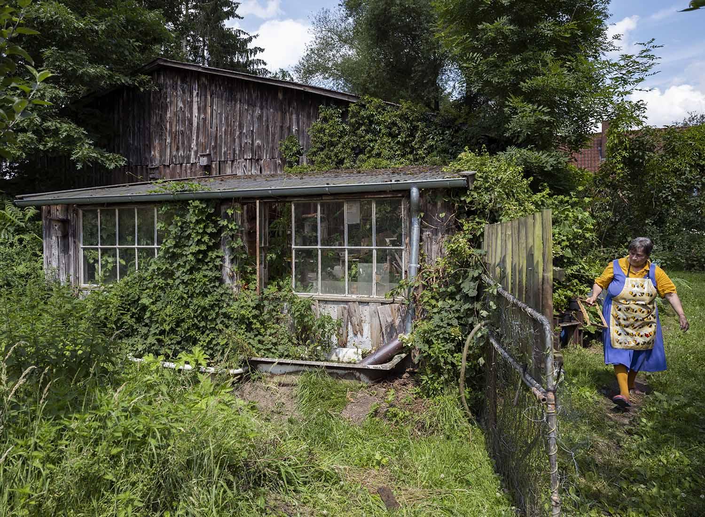 Birgit Wahlen verlässt das Gewächshaus in ihrem Garten auf dem Obsthof Wahlen. Sie trägt eine Wabe für ihre Bienen in der Hand, denn sie imkert auch.