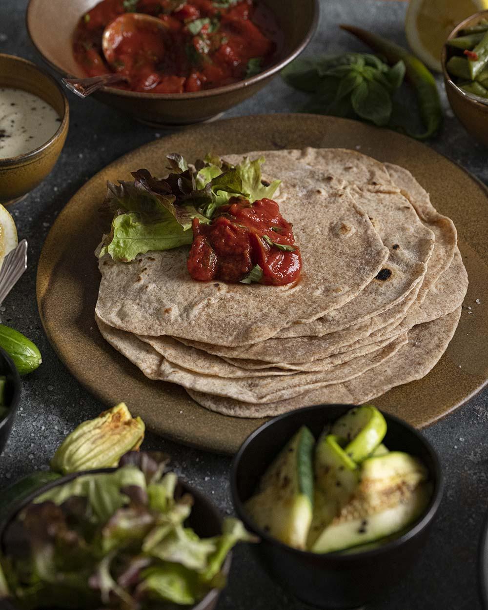 Wir haben einen Klecks Tomaten-Sugo auf einen unserer Wraps gegeben und ein Blatt Salat daneben gelegt. Gleich wikeln wir den Fladen ein.