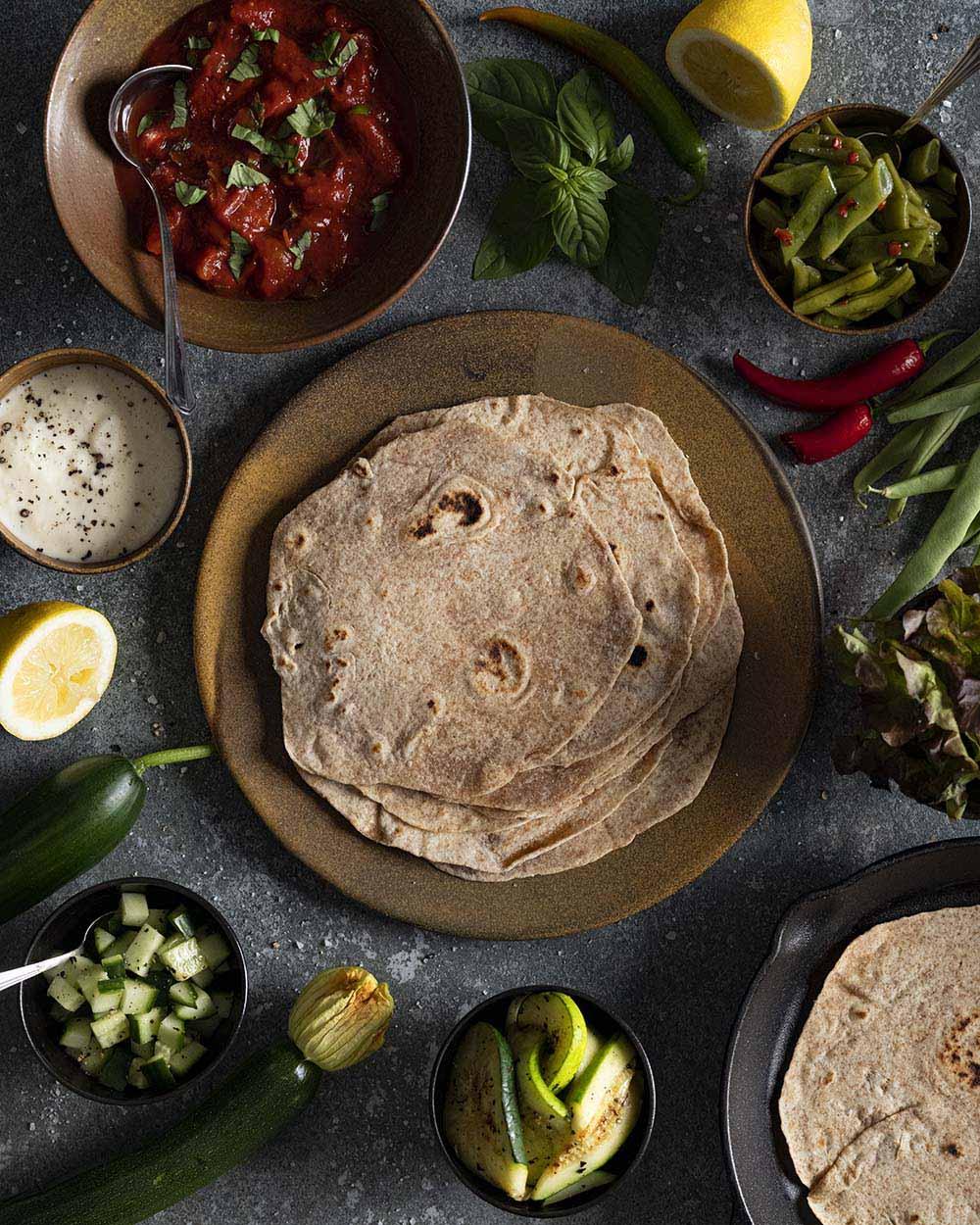 Aufnahme von oben: Zu sehen ist ein Teller, auf dem wir unsere selbst gemachten Wrpas gestapelt haben. Draumherum stehen Schalen mit verschiedenn Sorten Gemüse und einem Tomaten-Sugo, Zutaten, mit denen wir unsere Wraps belegen.