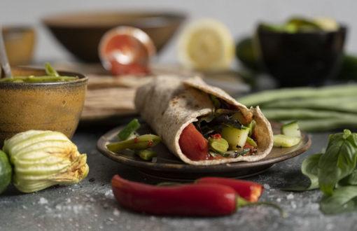 Unsere selbstgemachten Wraps sind fertig. Wir haben einen Wrap mit Gemüse befüllt und aufgerollt auf einen Teller gelegt.