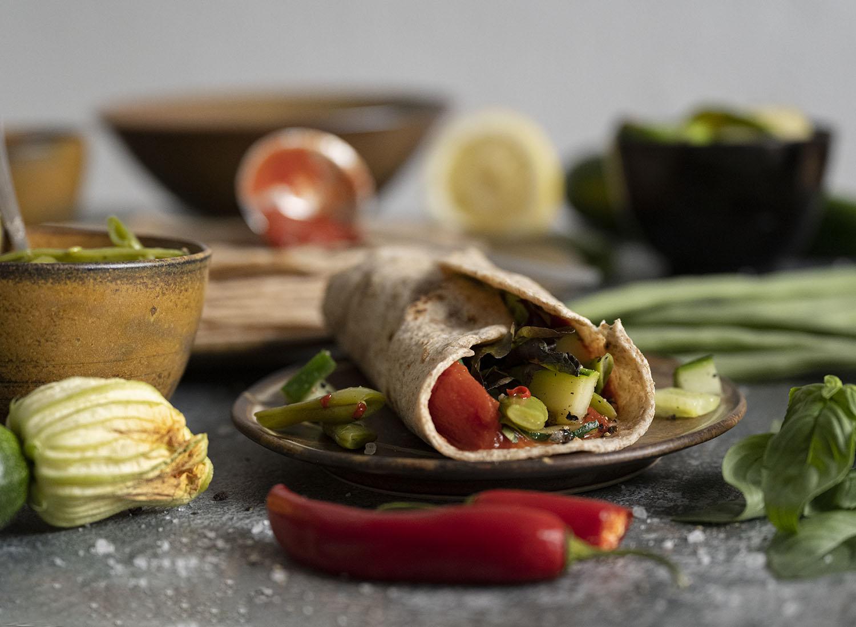 Wir haben den ersten gefüllten Wrap eingewickelt und auf einen Teller gelegt. Auf dem Tisch sind außerdem die verschiedenen Zutaten zu sehen, die wir als Füllung für unsere selbst gemachten Wraps nutzn.