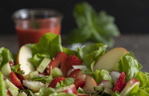 Unser Sommersalat ist angerichtet. Daneben steht ein Glas mit usnerem selbstgemachten Erdbeerdressing.