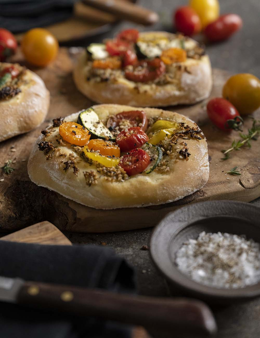 Nahaufnahme eines fertig gebackenen Zatar-Brotes mit Gemüse. Darauf sind Tomaten und Zuccini.