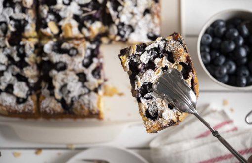 Mit einer Gebäckzange heben wir ein Stück Joghurtkuchen mit Blaubeeren aus dem ganzen Blechkuchen.