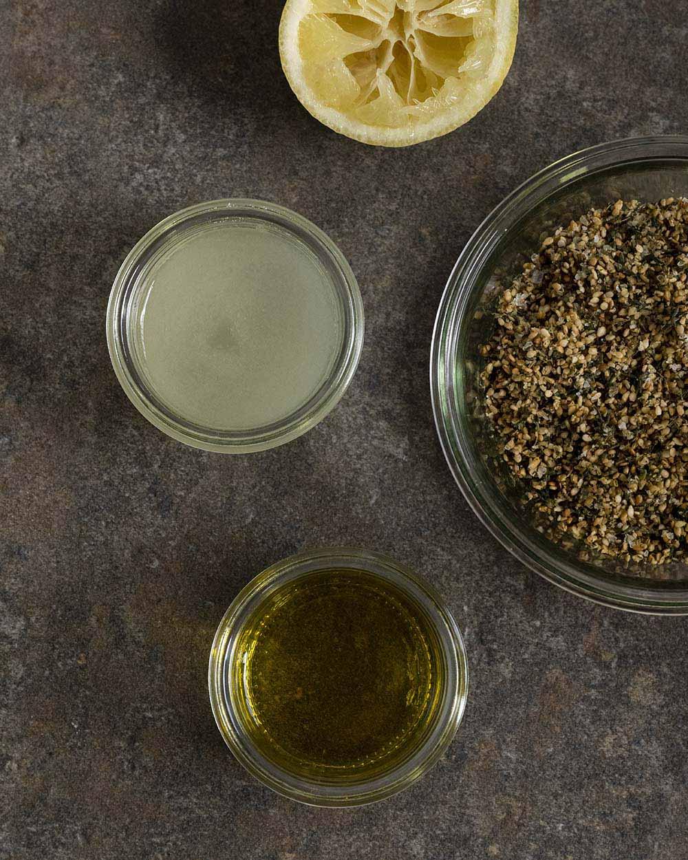 In einer Schüssel ist unser selbstgemachtes Zatar-Gewürz zu sehen. Daneben stehen zwei Gläser mit ausgepresstem Zitronensaft und Olivenöl, Zutaten, mit denen wir unser Gewrz gleich vermischen.