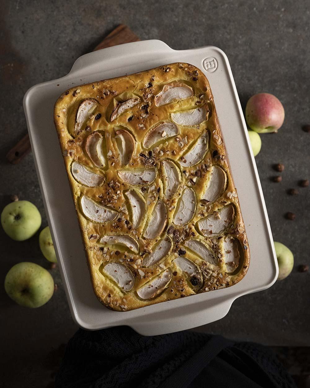 Unser Apfelpfannkuchen vom Blech, fotografiert von oben. Wir haben ihn auf eine Servierplatte gehoben. Noch ist er nicht angeschnitten und ohne Zimt und Zucker. Zu sehen sind di vielen Apfelspalten, die wir mit Schale im Teig verteilt haben.