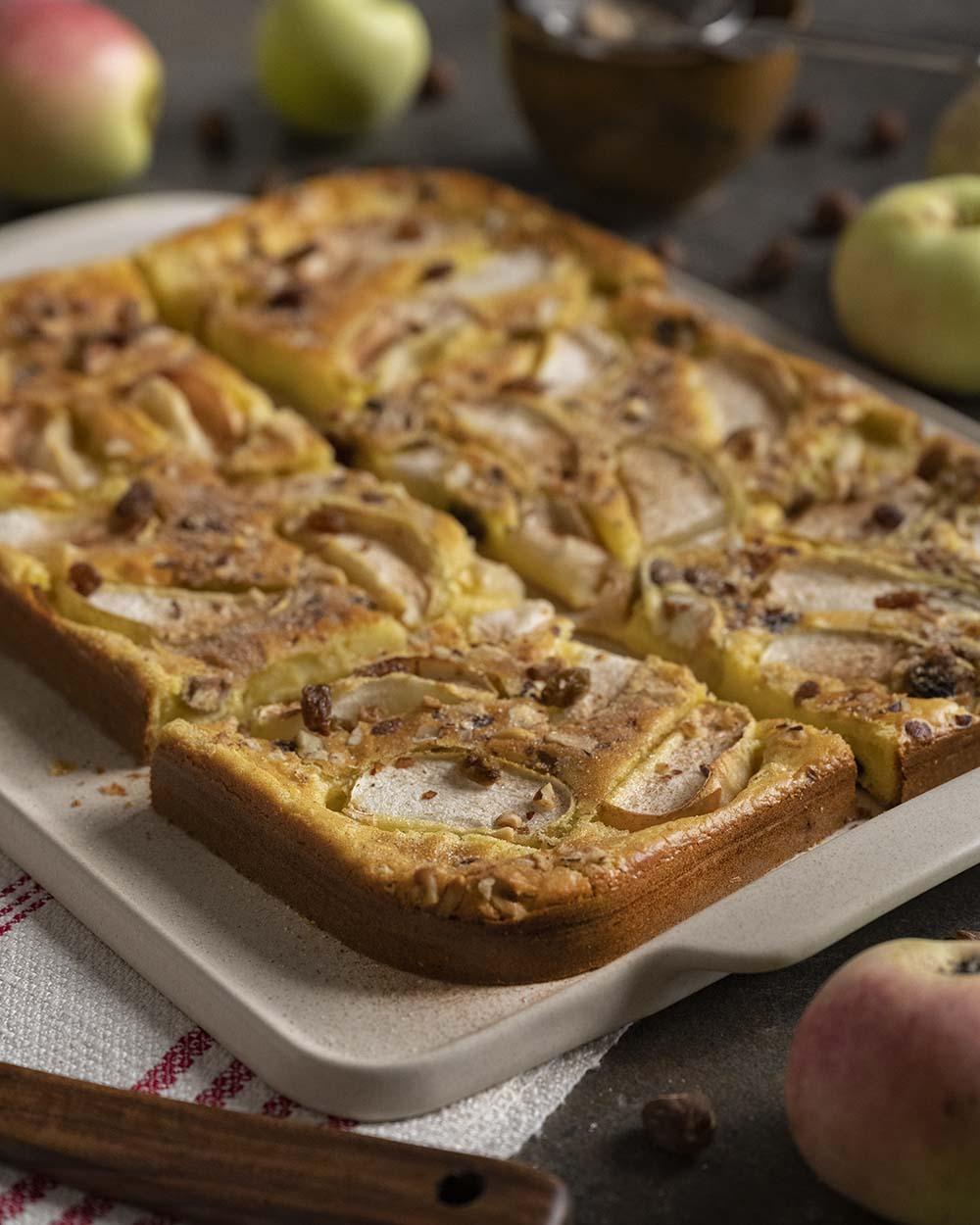 Die Servierplatte steht auf unserem Tisch. Darauf liegt der angeschnittene Apfelpfannkuchen, den wir im Ofen gebacken haben. Neben der Platte liegt ein Küchenhandtuch und ein Heber, mit dem wir gleich ein Stück Pfannkuchen von der Platte heben.
