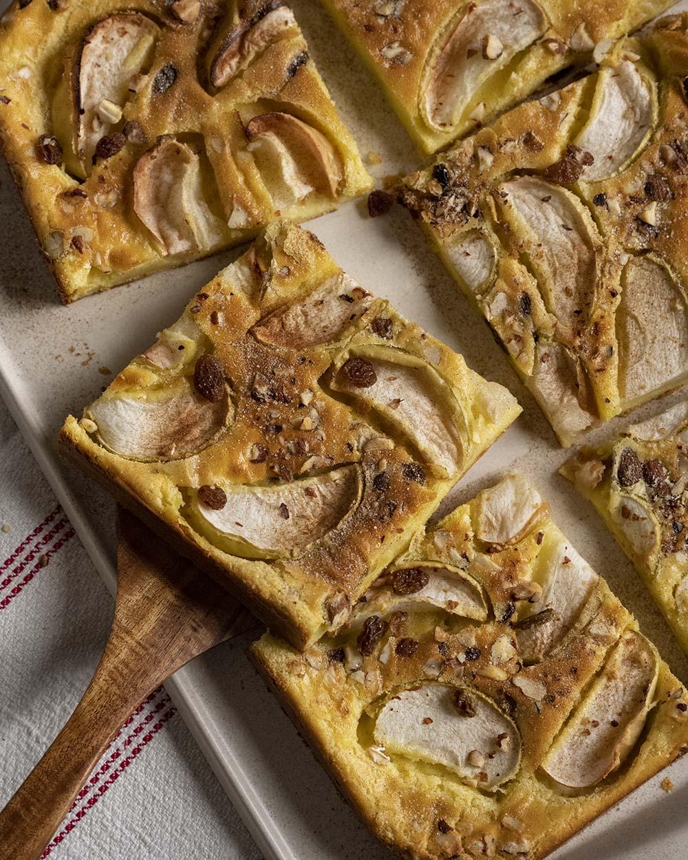 Wir haben ein Stück Apfelpfannkuchen auf einen Heber gelegt und heben das Stück gleich von der Servierplatte, auf der mehrre tücke des angeschnittenen Eierkuchens liegen.