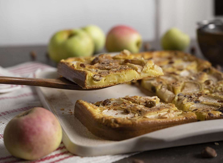 Zu sehen ist unser ganzer Tisch. Darauf steht die Servierplatte, daneben haben wir einige frische Äpfel der Sorte Fürst Blücher gelegt. Mit einem Tortenheber aus Holz heben wir ein Stück Apfelpfannkuchen hoch, den wir im Ofen auf dem Blech gebacken haben. Im Teig sind auch die Rosinen und Nüsse zu sehen, die wir zusätzlich in den Teig gemengt haben.