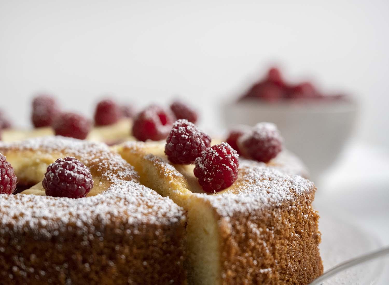 Abschlussbild: Wir zeige noch einmal die Oberfläche des ganzen Kuchens, in dem bereits der Tortenheber steckt. Oben auf den Himbeeruchen, in dessen Inneren sich mehrere Kleckse aus Quark verbergen, haben wir einzelne frische Himbeeren dekoriert und mit Puderzucker bestreut.