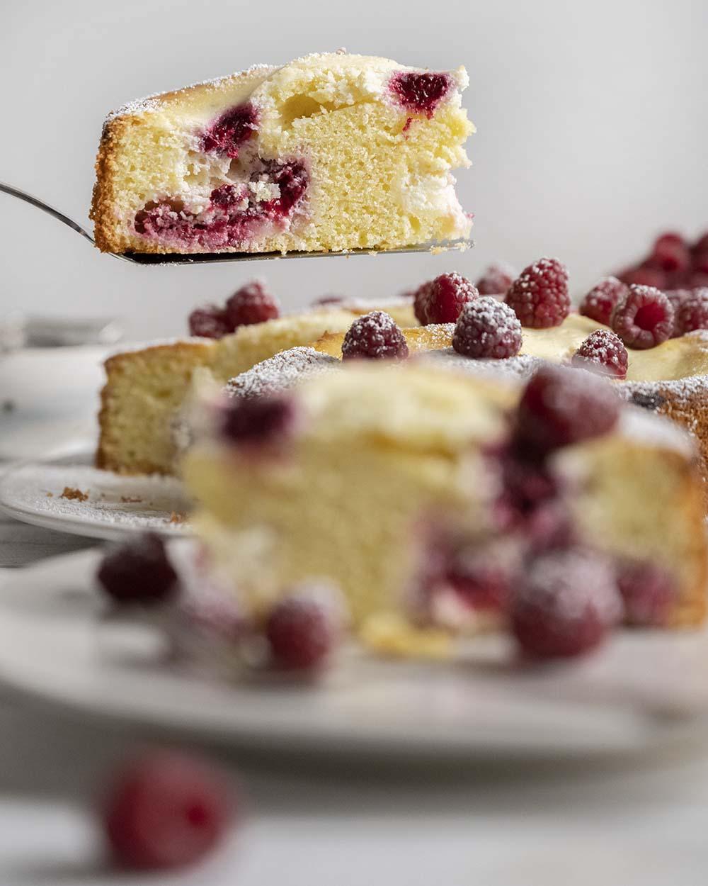 Mit dem Tortenheber heben wir ein Stück Himbeerkuchen aus dem ganzen Kuchen. Im Vordergrund ist bereits ein zweites Stück unscharf auf einem Teller zu erkennen.