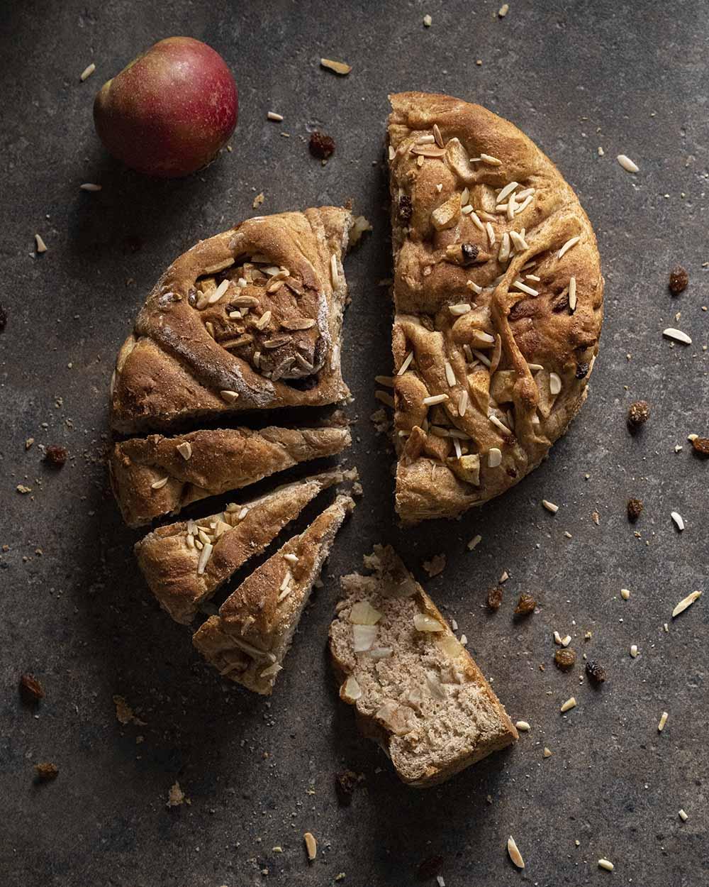 Angeschnittenes Apfelbrot auf dem Tisch. Neben dem Brot liegt ein Apfel. Eine Scheibe ist auf die Sete gedreht und zeigt, wie viele Apfelstücke im Brot enthalten sind.