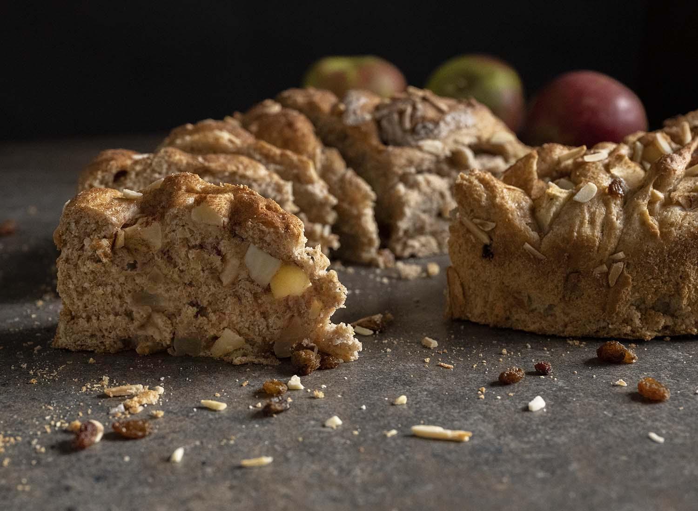 Angeschnittenes Apfelbrot auf dem Tisch. Wir haben auf ein STück angeschnittenes Brot fokussiert, das auf dem Tisch steht und viele Apfelstücke enthält.