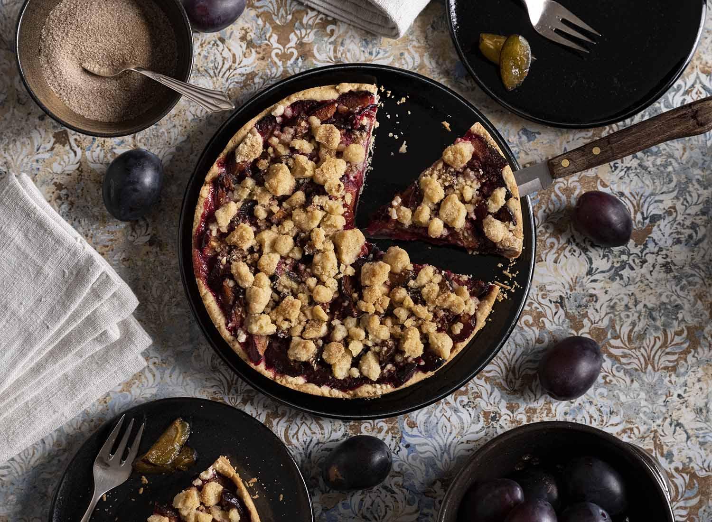 Die Kaffeetafel im Überblick, fotografiert von oben. Ein Stück Kuchen liegt bereits auf dem Teller, das andere heben wir gerade mit dem Messer heraus. Super lecker!