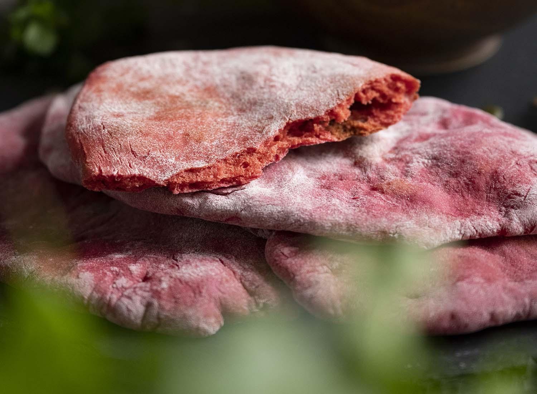 Close-Up-Foto von drei fertig gebackenen pinken Naan Broten. Sie liegen übereinandergestapelt. Das obere Brot ist durchgebrochen. Zu sehen ist wie fluffig das Innere ist.